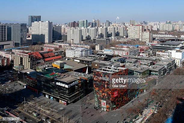 Shoppers walk through Sanlitun Village a popular shopping center by developer Soho in Beijing China on 10 December 2011
