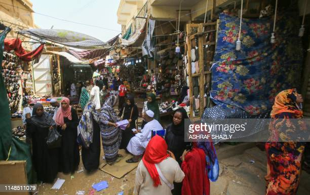 Shoppers walk through the main market of Omdurman, the Sudanese capital Khartoum's twin city, on June 8 a few days after heavily armed paramilitaries...