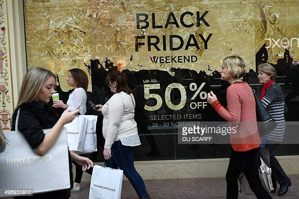 Shoppers walk through the Trafford Centre shopping mall past retailers offering 'Black Friday' discounts in Manchester northern England on November...