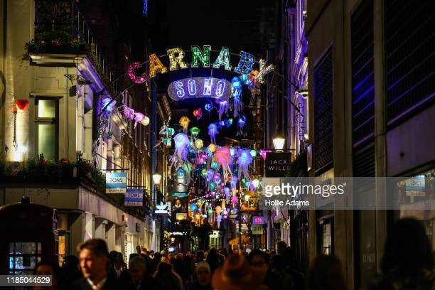 Shoppers walk under Christmas lights hanging on Carnaby Street on November 27 2019 in London England