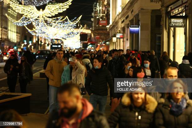 Shoppers walk under the Christmas lights on Regents Street in London on December 6, 2020. - Shoppers returned to Englands high streets this week as...