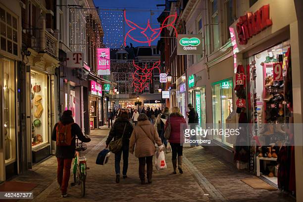 Shoppers walk underneath festive Christmas lights as logos for TMobile operated by Deutsche Telekom AG left and Specsavers Optical Group Ltd right...