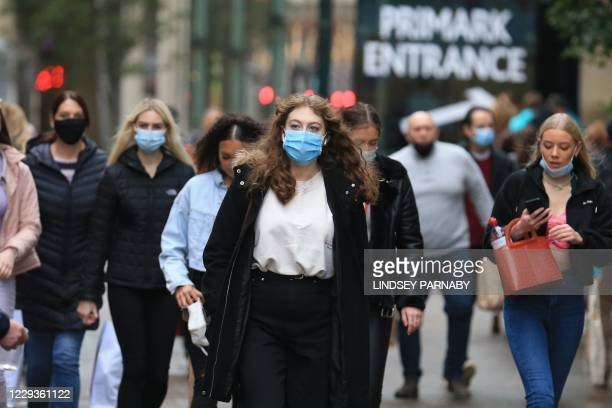 Shoppers walk wearing face masks in the centre of Leeds, West Yorkshire, northern England, on October 30, 2020 as the area prepares to be placed in...