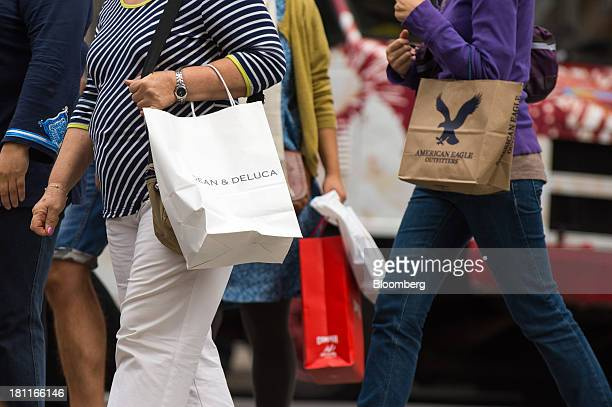 Shoppers walk with their shopping bags in the shopping district of Soho in New York US on Saturday Sept 14 2013 Consumers views of the US economic...