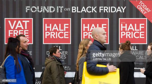 Shoppers walking past 'Black Friday' advertising in shop windows on Oxford Street in central London on November 28 2014 Police blasted stores for...
