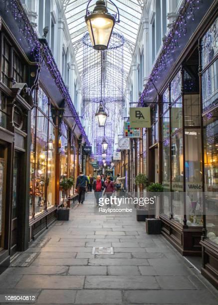 カーディフ ウェールズ英国のクリスマスの壊れ目の間に覆われたビクトリア朝の商店街を歩く買い物客 - カーディフ ストックフォトと画像