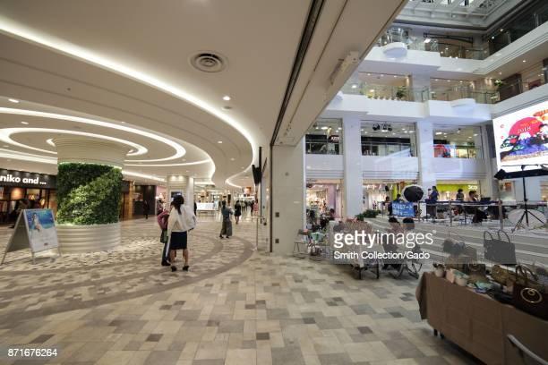 Shoppers walking through the interior of Ikebukuro Sunshine City a shopping complex in the Ikebukuro ward Toshima Tokyo Japan October 16 2017