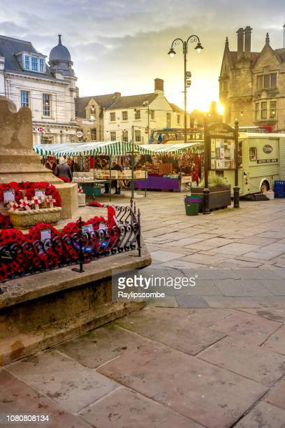 shoppers wandering around a monday market taking place under a setting evening sun in the cotswold capital of cirencester - cirencester stock pictures, royalty-free photos & images