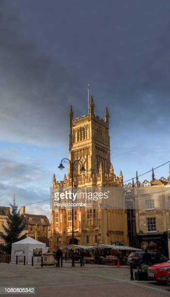 shoppers wandering around market stalls in cirencester, the cotswolds, beneath the parish church of st john the baptist bathed in an evening winter sunset - cirencester stock pictures, royalty-free photos & images