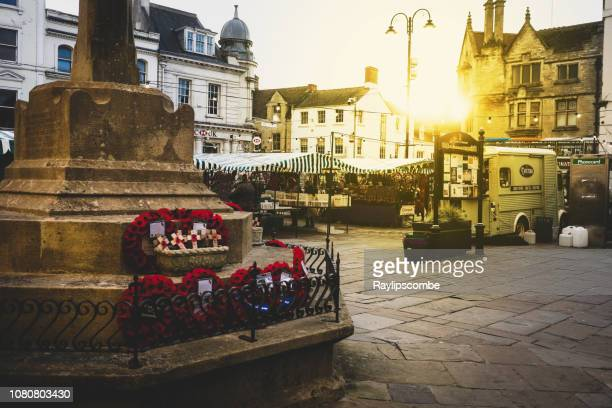 shoppers wandering around the cotswold capital of cirencester centre with a monday market taking place under a setting evening sun - cirencester stock pictures, royalty-free photos & images