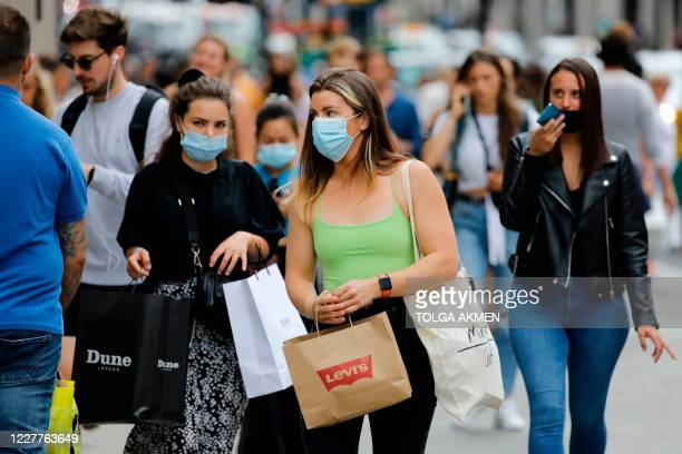 Shoppers wear face masks on Oxford Street om London on July 24 after wearing facemasks in shops and supermarkets became compulsory in England as a...