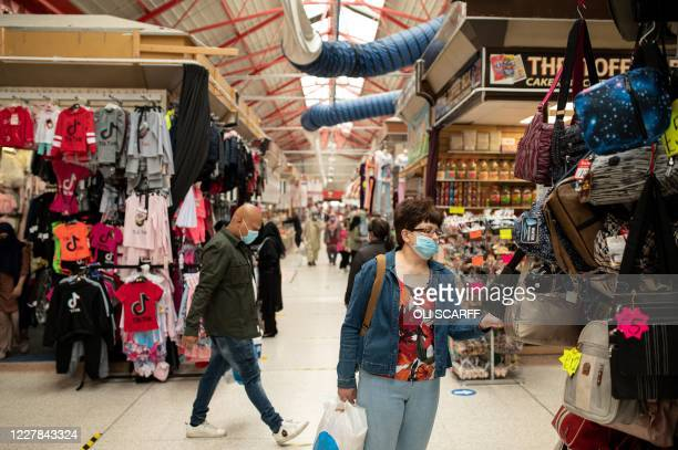 Shoppers wear facemasks as they inspect items for sale in Tommyfield Market in Oldham greater Manchester northwest England on July 30 2020