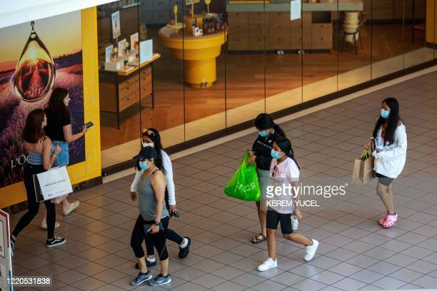 Shoppers wear facemasks at the Mall of America on June 16, 2020 in Bloomington, Minnesota, after some of the shops at the mall reopened on June 10. -...