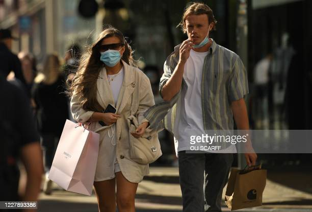 Shoppers wearing a face mask or covering due to the COVID19 pandemic walk along the street in Manchester northwest England on August 3 following a...