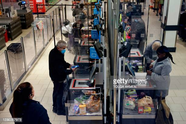 Shoppers wearing a face mask or covering due to the COVID-19 pandemic, pay for their goods at self-serve check-outs inside an Lidl supermarket in...