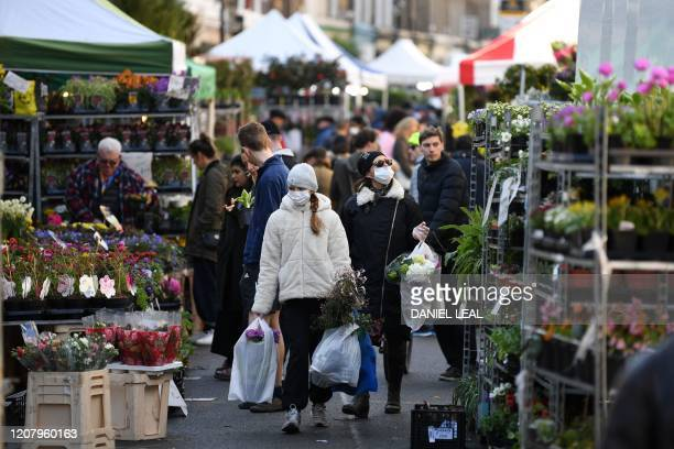 Shoppers wearing a protective face masks carry flowers after a visit to Columbia Road flower market in east London on Mother's Day March 22 2020 Up...