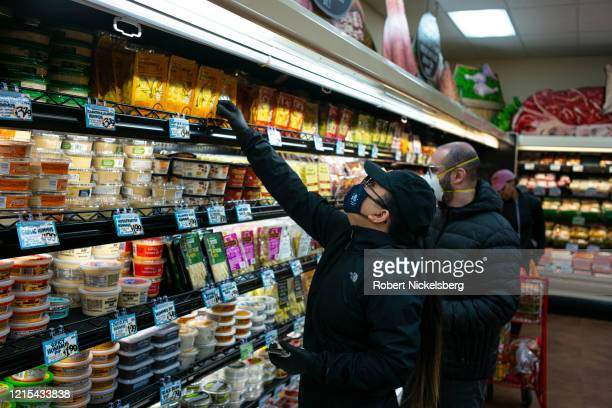 Shoppers wearing a surgical masks look at a prepared meals at a Trader Joes in Brooklyn New York on March 28 2020 The store lets in a minimum amount...
