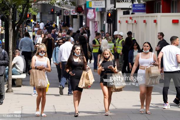 Shoppers wearing face coverings due to Covid-19, but pulled down under their chin, walk along Oxford Street in central London on June 7, 2021. - The...