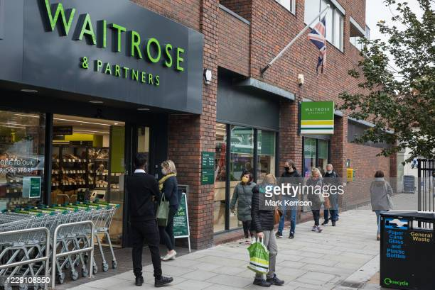 Shoppers wearing face coverings to help prevent the spread of the coronavirus queue outside a Waitrose store on 16 October 2020 in Weybridge, United...