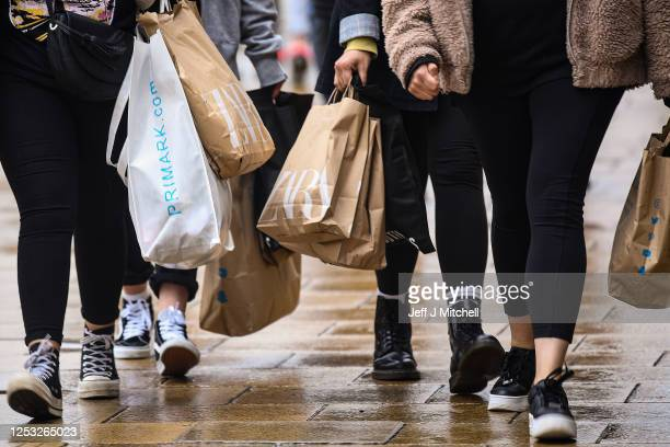 Shoppers wearing face masks and carrying shopping bags walk along Princess Street as the Scottish Lockdown eases and shops reopen on June 29, 2020 in...