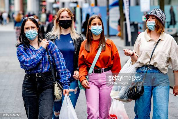 Shoppers wearing face masks as a preventive measure walk on the street during the coronavirus crisis. The wearing of a face mask will become...