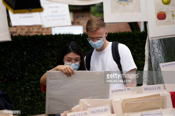 Shoppers wearing face masks browse at Portobello Road market in Notting Hill, west London on July 31, 2021. - Coronavirus case numbers increased more...