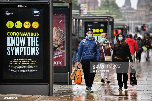Shoppers wearing face masks walk along Princess Street as the Scottish Lockdown eases and shops reopen on June 29, 2020 in Edinburgh, Scotland. Shops...