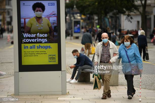 Shoppers wearing face masks walk past a sign calling for the wearing of face coverings in shops, in the city centre of Sheffield, south Yorkshire on...