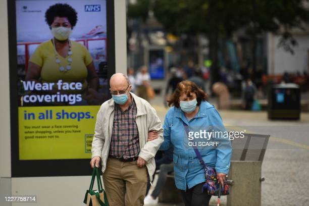 Shoppers wearing face masks walk past a sign calling for the wearing of face coverings in shops in the city centre of Sheffield south Yorkshire on...