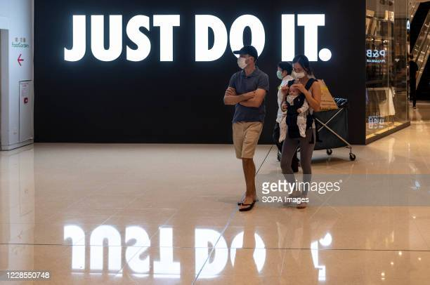 """Shoppers wearing face masks walk past an American multinational sport clothing brand Nike store, logo, with a slogan """"Just Do It"""" in Hong Kong."""