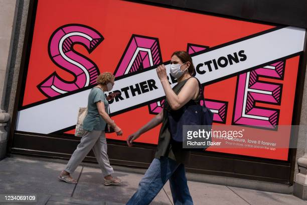 Shoppers wearing face masks walk past Selfridges whose Summer Sale is advertised in their window banners on Oxford Street in the West End on Covid...