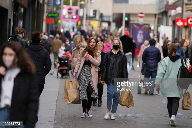 Shoppers wearing face masks walk through the streets of Nottingham on 28 October 2020.