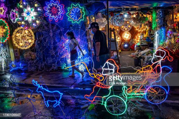 Shoppers wearing facemasks and face shields to protect against COVID-19 walk past Christmas lanterns for sale at a Christmas decorations market on...