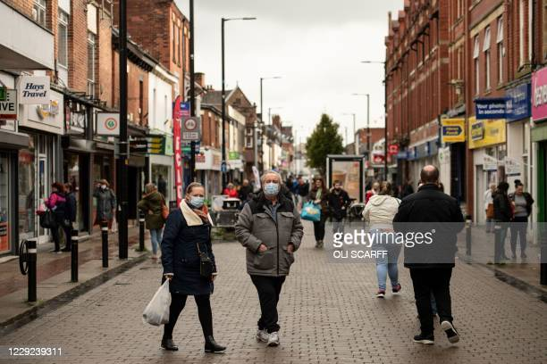 Shoppers, wearing facemasks because of the novel coronavirus pandemic, walk in the High Street of Leigh, Greater Manchester, northwest England on...
