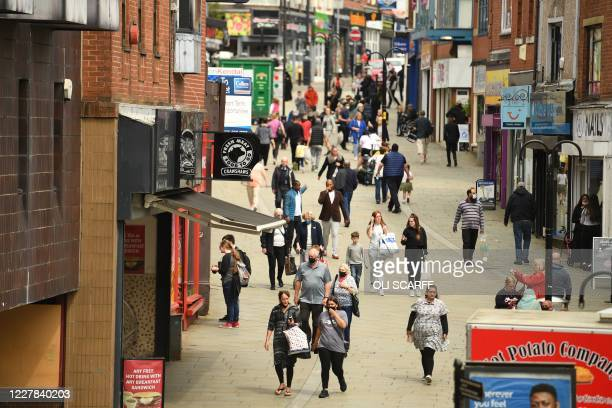 Shoppers wearing facemasks walk through central Rochdale greater Manchester northwest England on July 30 2020 Rochdale reportedly faces harsher...