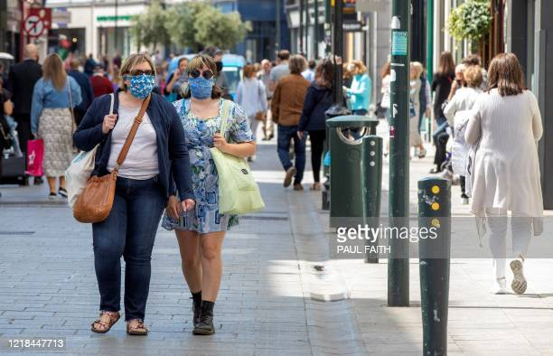 Shoppers wearing homemade PPE face masks or face coverings as a precautionary measure against COVID19 walk past reopened shops in Grafton Street in...