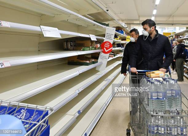 Shoppers wearing masks are faced with partially empty shelves at a supermarket in London on March 14 as consumers worry about product shortages...