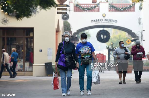 Shoppers wearing masks to protect themselves from smoke and ash from the Thomas Fire walk on State Street the main shopping street in Santa Barbara...