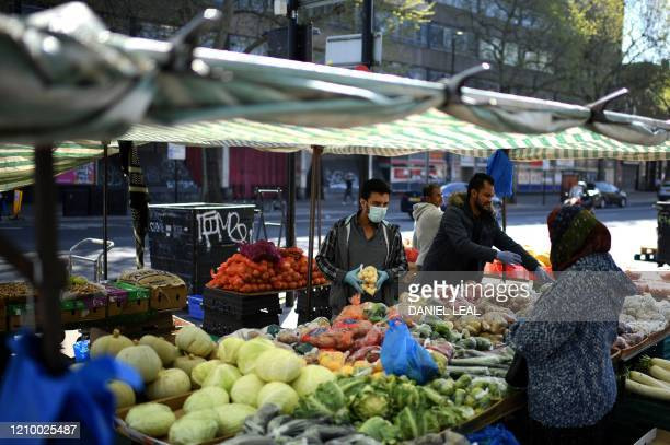 Shoppers wearing PPE including a face mask and gloves as a precautionary measure against COVID-19, buy fruit and vegetables from stall holders at...
