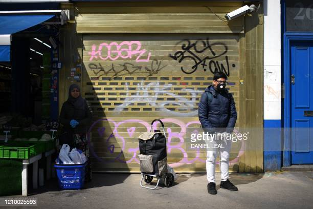 Shoppers wearing PPE including a face mask and gloves as a precautionary measure against COVID-19, stand by the shuttered frontage of a closed-down...