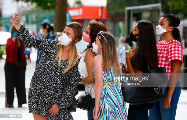 Shoppers wearing PPE , of a face masks or coverings as a precautionary measure against spreading COVID-19, pose for a selfie photograph as they queue...