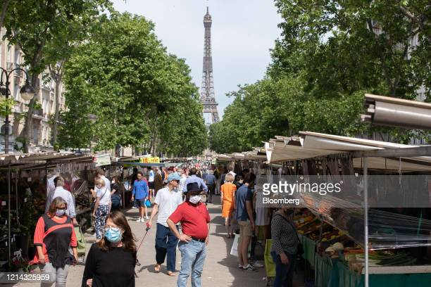 Shoppers wearing protective face masks pass fruit and vegetable market stalls near the Eiffel Tower monument at Marche SaxeBreteuil in Paris France...