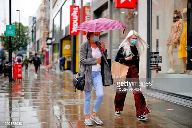 Shoppers wearing protective face masks walk through the rain on Oxford Street in London on June 18 as some non-essential retailers reopen from their...