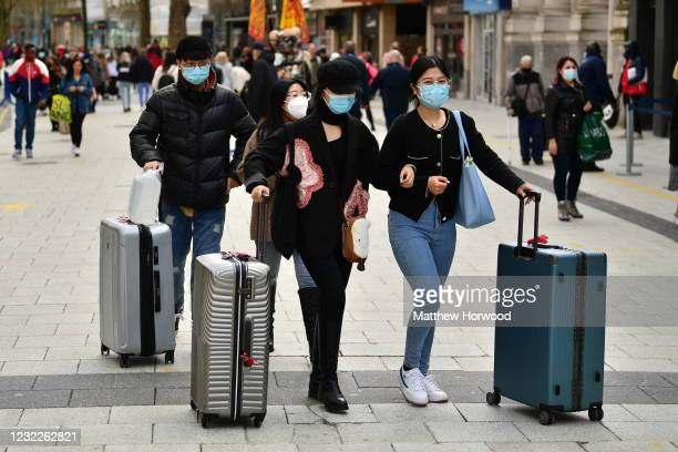 Shoppers wheel suitcases through Queen Street as non-essential retail reopens on April 12, 2021 in Cardiff, Wales. Lockdown restrictions have been...