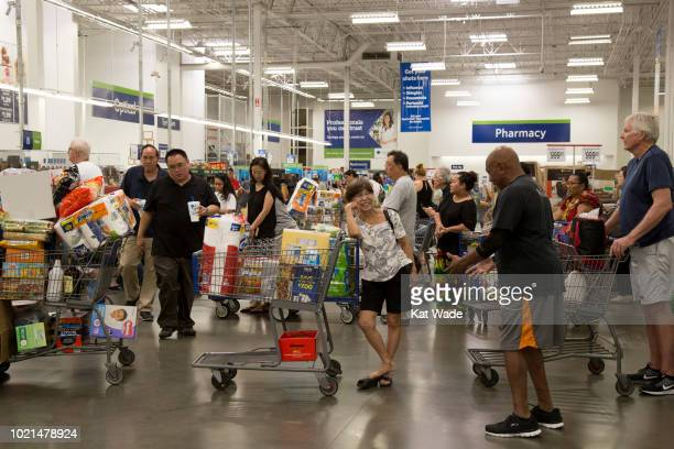 Shoppers with heavily weighted shopping carts wait in line to purchase supplies for Hurricane Lane at Sam's Club on Wednesday August 22 2018 in...