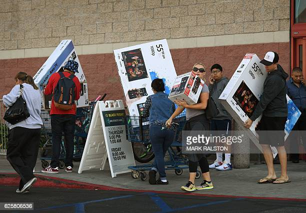 Shoppers with their arms full walk to their cars during the 'Black Friday' sales at a Best Buy store in Culver City California on November 25 2016 US...