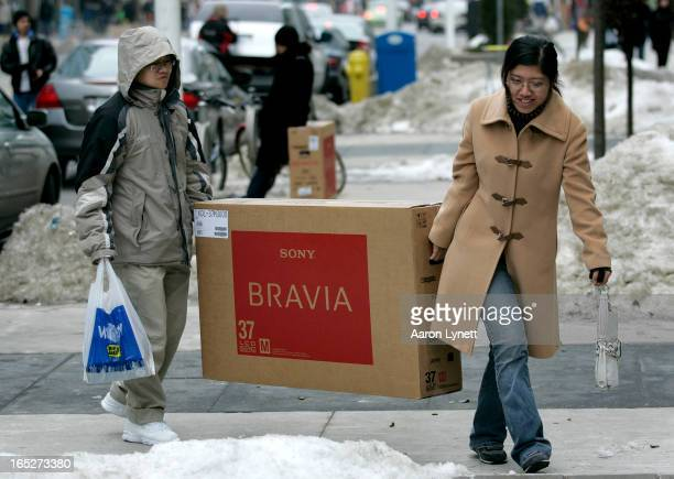 Wenbin Kong and Shelly Cao of Toronto carry a newly purchased television to their car on Dundas St West Wednesday afternoon December 26 2007 The two...