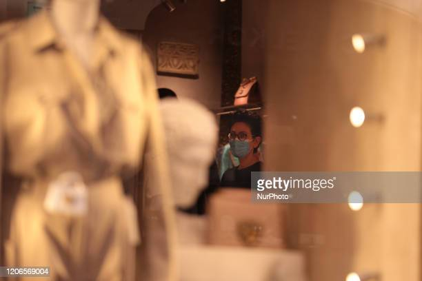 Shopping assistant from a high fashion store wears a protective mask during the Coronavirus emergency, on March 11 in Rome, Italy. The Italian...