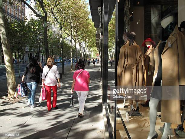 Shopping at Calle Serrano in Madrid several young loaded with bags walking next to the window of a luxury fashion store Salamanca district of Madrid...