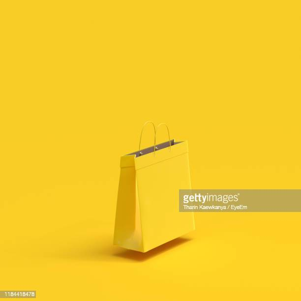 shopping bag against yellow background - 買い物袋 ストックフォトと画像
